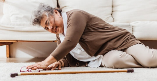 Asian senior woman falling down lying on floor at home alone. Elderly woman pain and hurt from osteoporosis sickness or heart attack. Old adult life insurance with health care and treatment concept